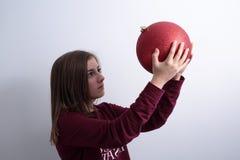 Adolescente con una bola de la Navidad Foto de archivo