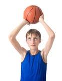 Adolescente con una bola para el baloncesto sobre su su cabeza Aislado en el fondo blanco Imágenes de archivo libres de regalías