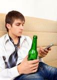 Adolescente con una cerveza y un teléfono móvil Fotografía de archivo