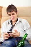 Adolescente con una cerveza y un teléfono móvil Fotos de archivo