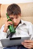 Adolescente con una cerveza y una tableta Fotos de archivo