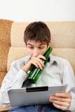 Adolescente con una cerveza y una tableta Fotos de archivo libres de regalías
