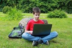 Adolescente con una computadora portátil en el parque Fotos de archivo libres de regalías