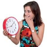 Adolescente con una expresión sorprendida que comprueba el tiempo en un reloj grande Fotos de archivo libres de regalías