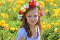 Adolescente con una guirnalda de flores coloridas en su cabeza Foto de archivo libre de regalías