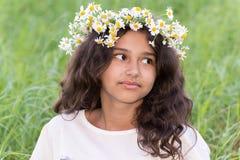 Adolescente con una guirnalda de margaritas en Imagen de archivo