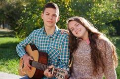 Adolescente con una guitarra y una muchacha Fotografía de archivo