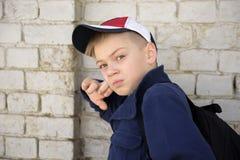 Adolescente con una mirada pensativa Pared de ladrillo del fondo Fotos de archivo