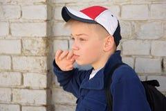 Adolescente con una mirada pensativa Pared de ladrillo del fondo Foto de archivo