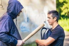 Adolescente con una mochila contra hombre agresivo Foto de archivo