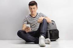 Adolescente con una mochila que mira un teléfono Foto de archivo