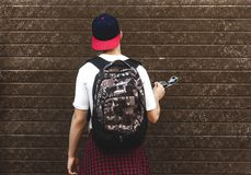 Adolescente con una mochila que se coloca cerca de una pared Imágenes de archivo libres de regalías