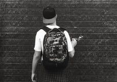 Adolescente con una mochila que se coloca cerca de una pared Imagenes de archivo