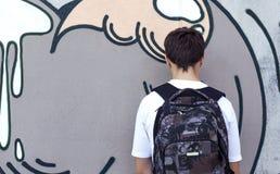 Adolescente con una mochila que se coloca cerca de una pared Foto de archivo