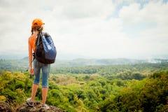 Adolescente con una mochila que se coloca en un top de la montaña Fotos de archivo libres de regalías