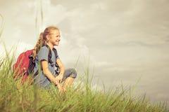 Adolescente con una mochila que se sienta en la hierba Imagen de archivo libre de regalías