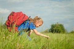 Adolescente con una mochila que se sienta en la hierba Imagenes de archivo
