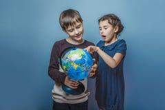 Adolescente con una muchacha que mira a una muchacha del globo Imágenes de archivo libres de regalías