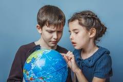 Adolescente con una muchacha que mira a una muchacha del globo Fotografía de archivo