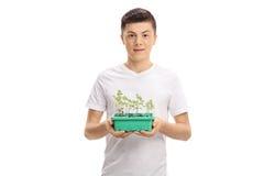 Adolescente con una planta en un pote Imagen de archivo libre de regalías