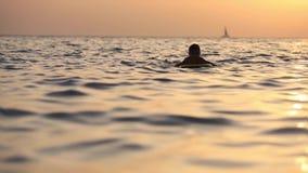 Adolescente con una tabla hawaiana en el fondo de la c?mara lenta completa de las olas oce?nicas HD almacen de video