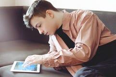 Adolescente con una tableta que miente en el sofá Imagen de archivo