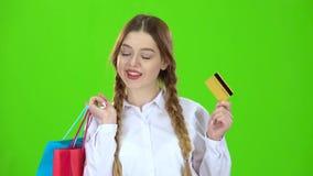 Adolescente con una tarjeta de crédito y paquetes en sus manos Pantalla verde almacen de video
