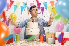 Adolescente con una torta de cumpleaños y un cuerno del partido Fotos de archivo libres de regalías