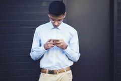 Adolescente concentrado apuesto en mensajería de las lentes con los amigos Fotos de archivo