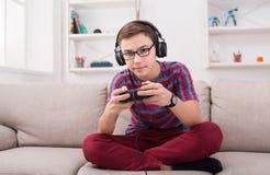 Adolescente concentrado que joga o jogo de vídeo em casa Fotografia de Stock Royalty Free