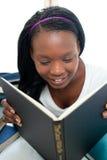 Adolescente concentrado que lee un libro Fotografía de archivo