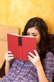 Adolescente concentrado que miente en cama y que lee un libro Fotos de archivo