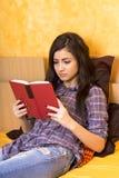 Adolescente concentrado que miente en cama y que lee un libro Imagen de archivo libre de regalías