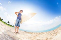 Adolescente confiado en la playa con la tabla hawaiana Foto de archivo
