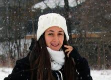 Adolescente confiado hermoso de los ojos verdes que camina debajo de nieve mientras que nieva Foto de archivo