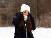 Adolescente confiado hermoso de los ojos verdes que camina debajo de nieve mientras que nieva Fotos de archivo