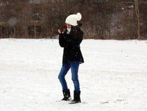 Adolescente confiado hermoso de los ojos verdes que camina debajo de nieve mientras que nieva Fotografía de archivo