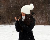 Adolescente confiado hermoso de los ojos verdes que camina debajo de nieve mientras que nieva Fotografía de archivo libre de regalías