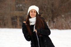 Adolescente confiado hermoso de los ojos verdes que camina debajo de nieve mientras que nieva Fotos de archivo libres de regalías