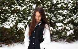 Adolescente confiado hermoso de los ojos verdes que camina debajo de nieve mientras que nieva Imagen de archivo