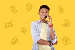Adolescente confiado que discute los dispositivos modernos mientras que habla en el teléfono Foto de archivo libre de regalías