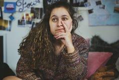Adolescente confiado que se sienta en un dormitorio Foto de archivo libre de regalías