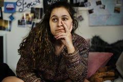 Adolescente confiado que se sienta en un dormitorio con un signo de la paz Fotos de archivo libres de regalías