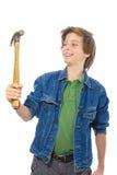 Adolescente confiado que sonríe a un martillo en su mano, aislada Imagen de archivo libre de regalías