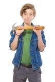 Adolescente confiado que sostiene un martillo en el frente, aislado en whi Foto de archivo