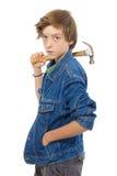 Adolescente confiado que sostiene un martillo en su hombro, aislado Imagen de archivo libre de regalías