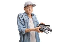 Adolescente confuso con los telecontroles Foto de archivo libre de regalías