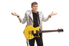 Adolescente confuso con una guitarra eléctrica Imágenes de archivo libres de regalías