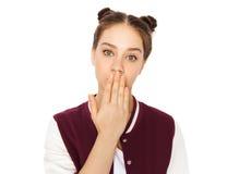 Adolescente confuso que cubre su boca a mano Foto de archivo