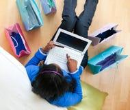 Adolescente consideravelmente afro-americano usando um portátil em casa Fotos de Stock